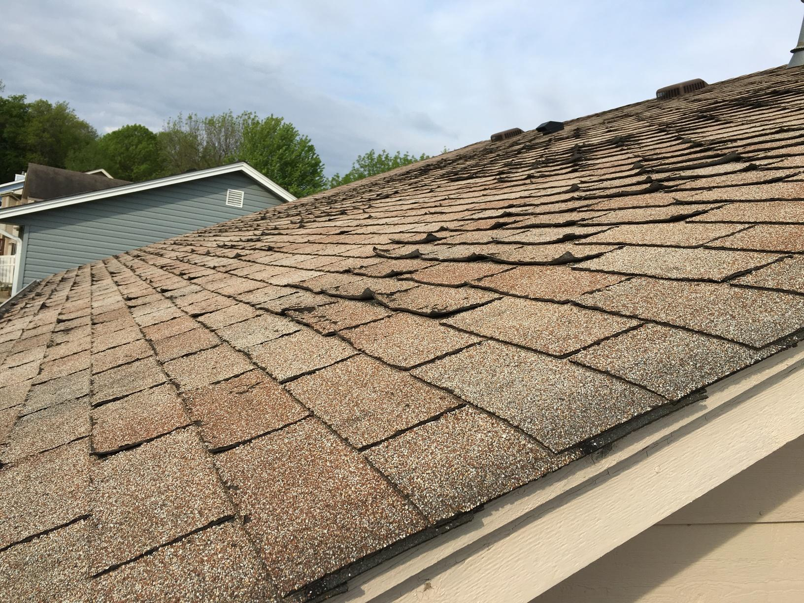 A before photo of the roof before replacement. Notice the cracking and curling shingles.