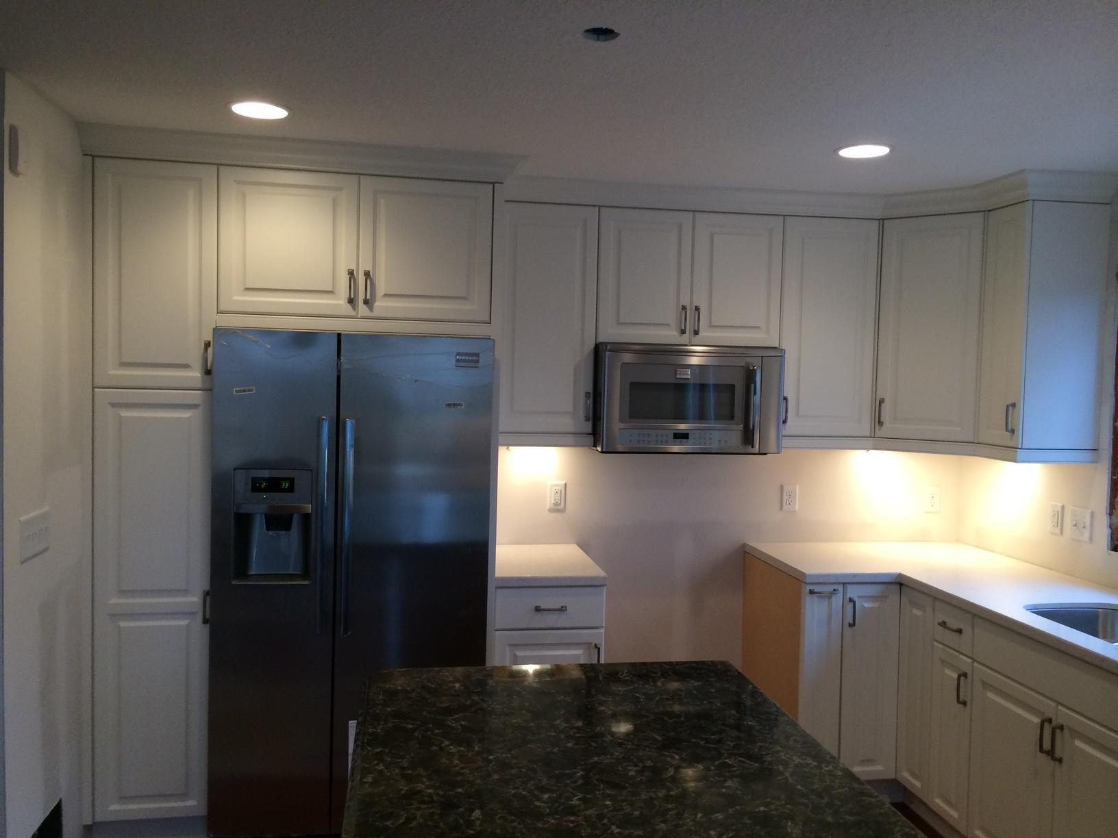 Newly remodeled kitchen with stainless steel microwave and refrigerator.